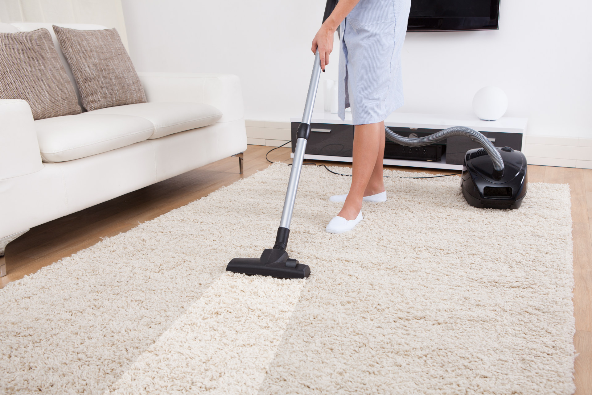 Woman cleaning the carpet with vacuum