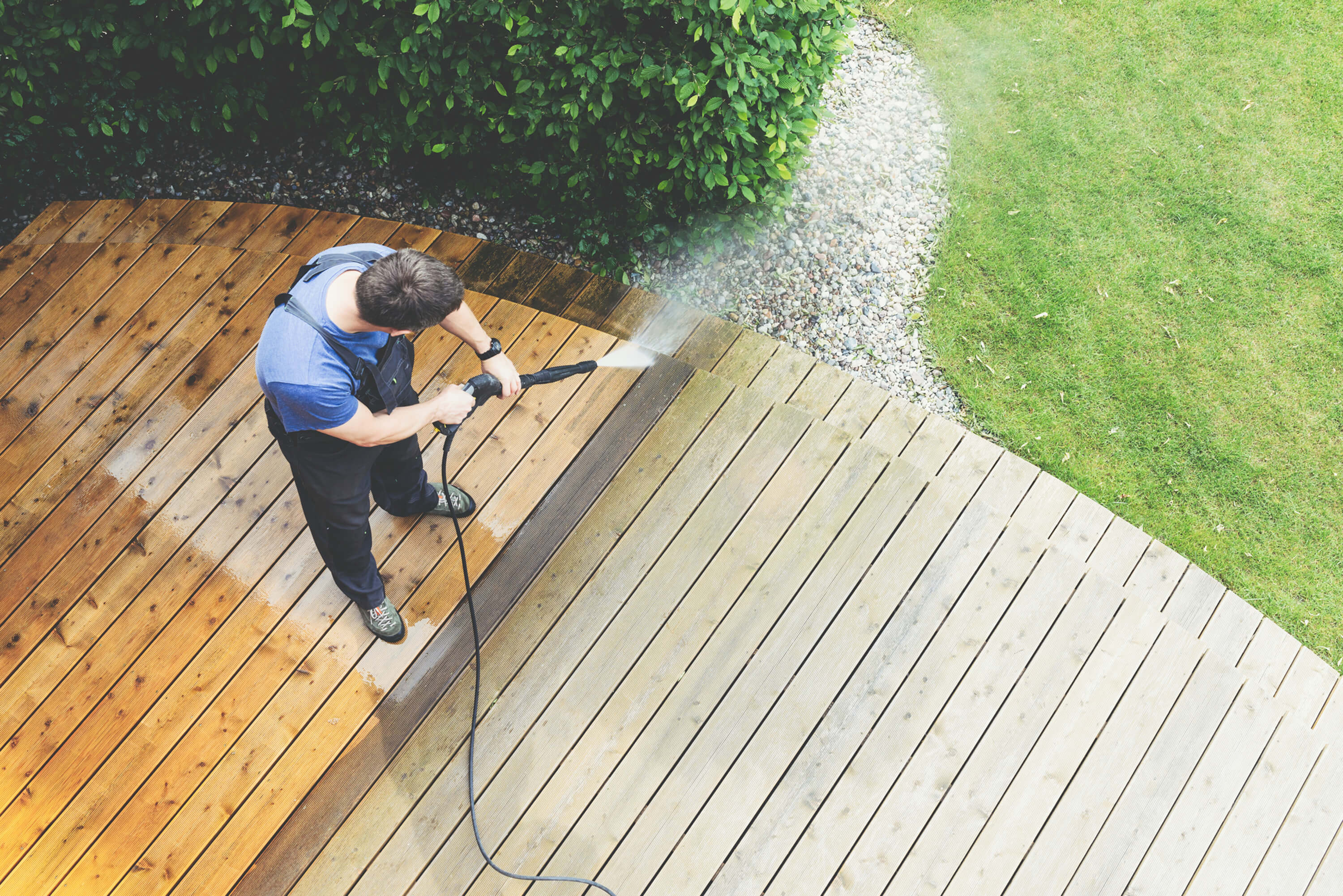 man pressure cleaning the deck