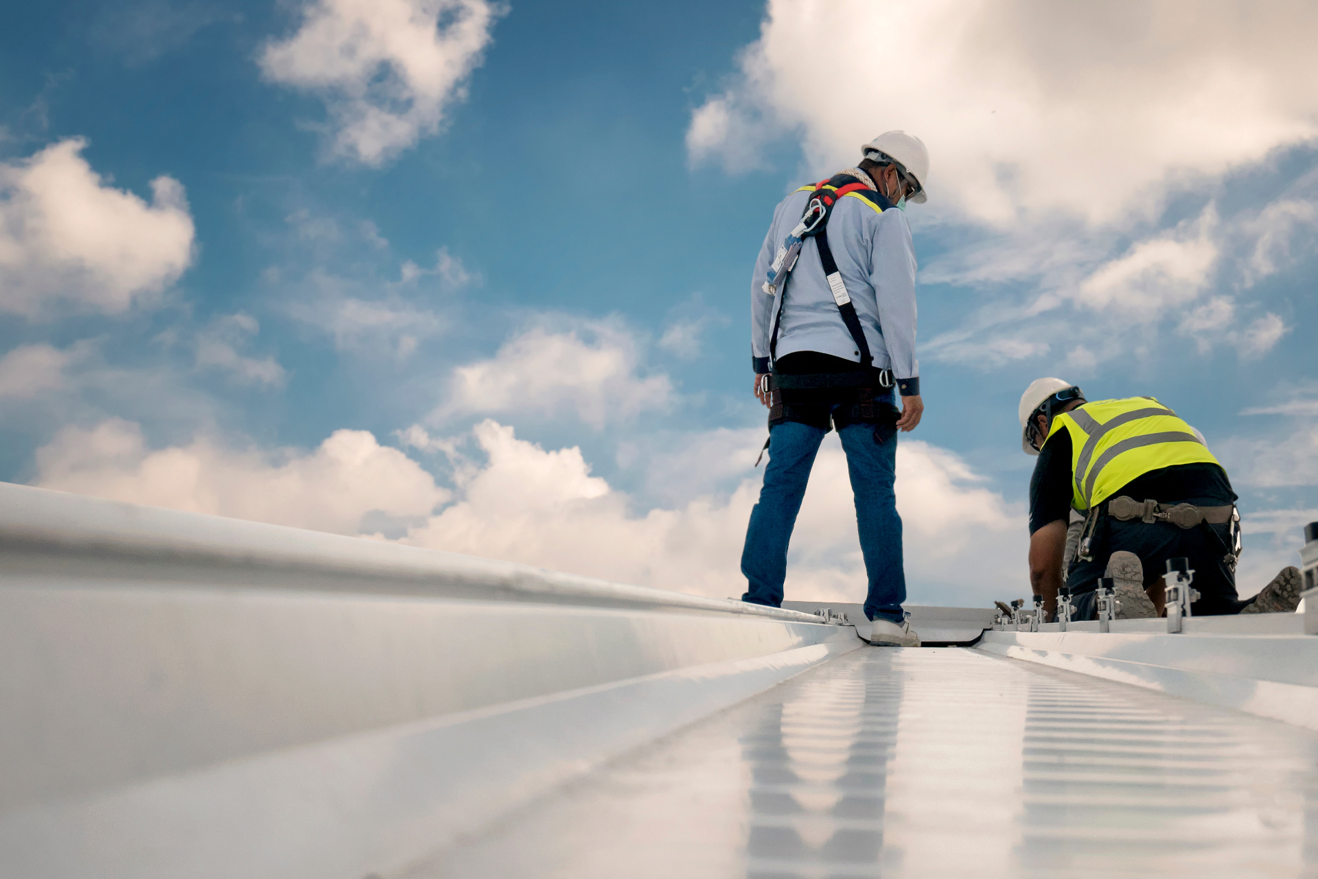 Two roofers working on white roof