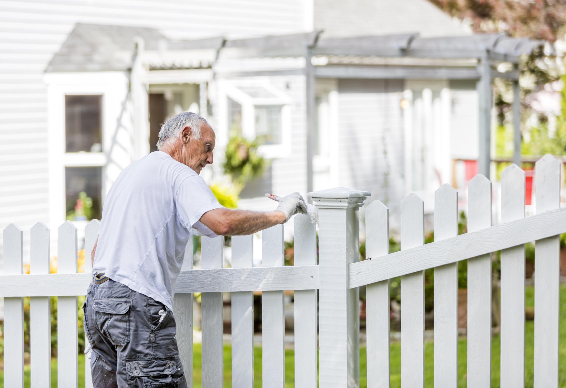 White man painting white fence