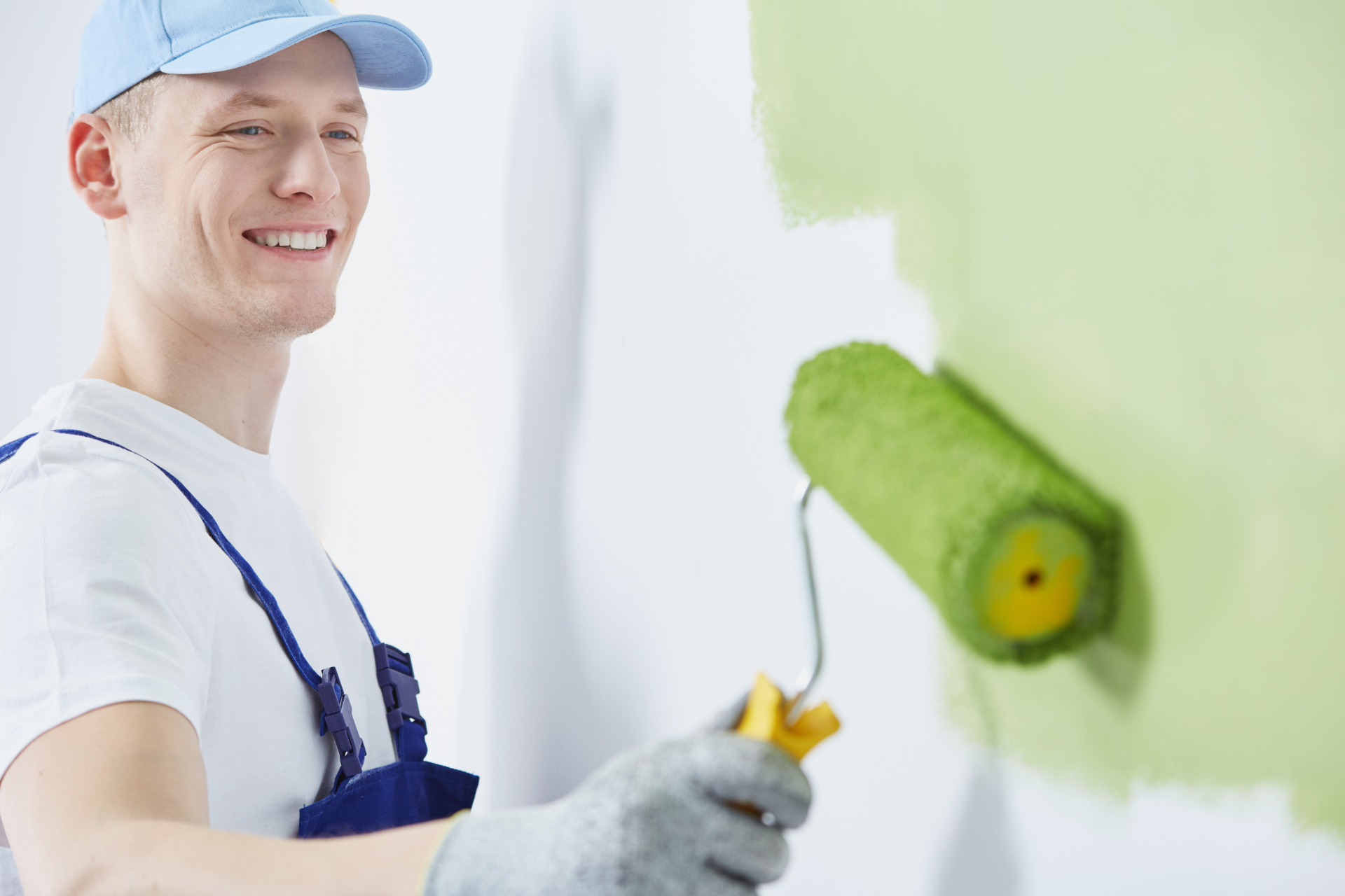 Painter painting with green paint roller